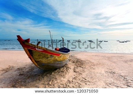 the free-standing fishing boat on a sandy beach and the dark blue sea with clouds - stock photo