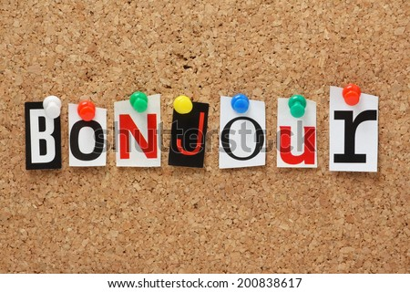 The French word Bonjour in cut out magazine letters pinned to a cork notice board