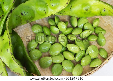 The fresh Parkia is tropical stinking edible beans in weave basket on weave tray  - stock photo