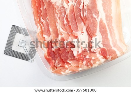 The fresh slide bacon in food grade transparent packaging and rfid tag represent the raw material and meat concept related idea.
