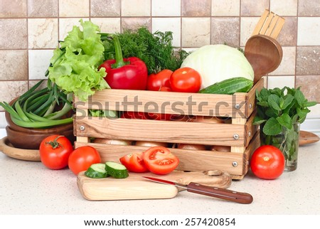 The fresh washed-up vegetables in a wooden box and the cut vegetables on a chopping board against modern kitchen. - stock photo