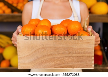 The freshest tangerines. Cropped image of young woman in apron holding wooden container with tangerines while standing in grocery store with variety of fruits in the background  - stock photo