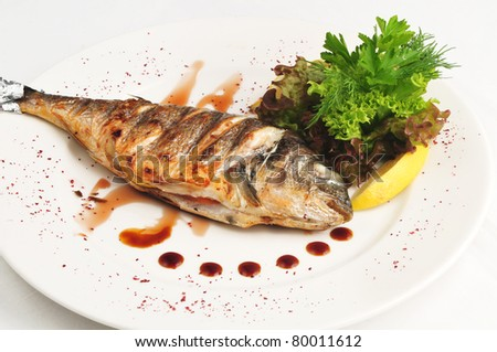 The fried fish with sauce and salad on a white plate - stock photo