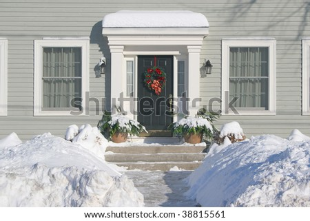 The front door of a residential family home decorated with a Christmas wreath. - stock photo
