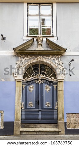 The front door to the old house with stucco decorations - stock photo