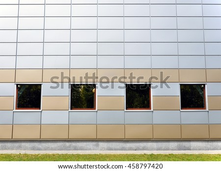 The front facade of a modern building of gray and yellow sandwich-panels with four square windows. Architectural background. - stock photo