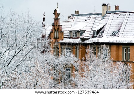 The front of a large older home  and trees covered in fresh snow in Stuttgart, Germany - stock photo