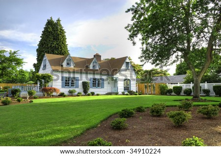 The front of a nicely kept family home with a green lawn and a tree to the right. - stock photo