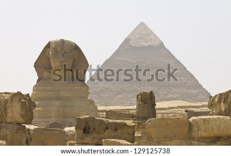 The front of the great Sphinx and the pyramid of Khafre and Menkaure behind it - stock photo