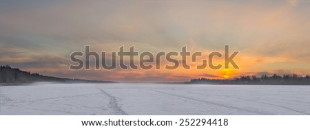 The frozen lake in the winter at sunset. Panorama - stock photo