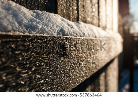 the frozen wooden fence. snow. the sun. transfused