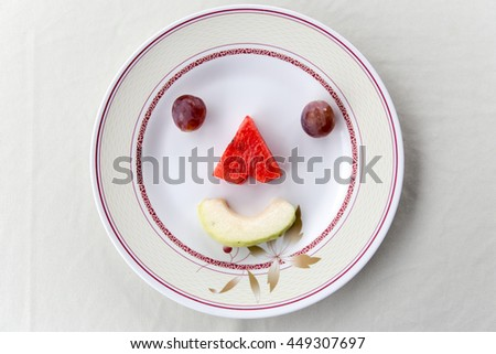 The fruit making up a smiling face on a plate.