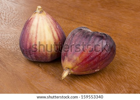 The fruits of fig tree on a wooden surface. - stock photo