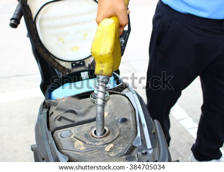 The fuel refill to the motorcycle selective focus with the pump tube - stock photo