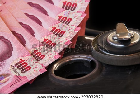 The fuel tank Motorcycle and hundred banknotes of Thailand (Thai baht). Closeup Photo. - stock photo