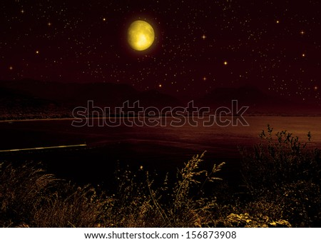 The full moon in the night sky reflected in water - stock photo