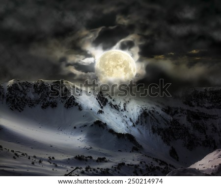 The full moon in the sky over the mountain snow peak in Krasnaya Polyana Sochi - stock photo