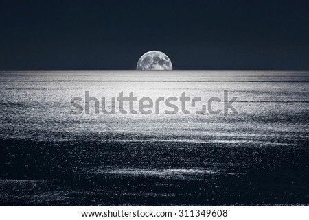The Full Moon sets into the calm waters of the Mediterranean Sea - stock photo