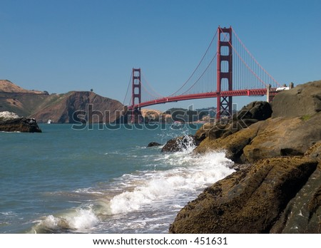 The full span of the Golden Gate Bridge with the rocks and surf of Baker's Beach in the foreground.