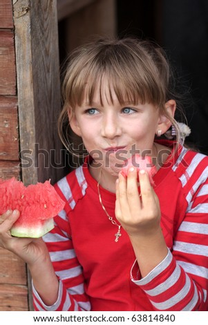The funny girl eats watermelon outdoor at autumn