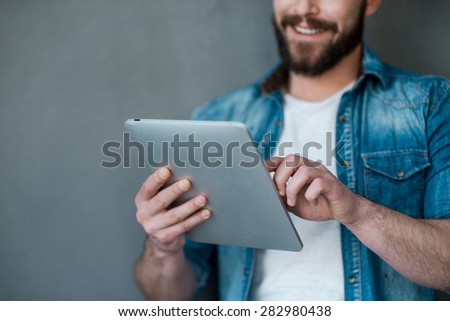 The future is in the touch. Cropped image of young man holding digital tablet and smiling while standing against grey background - stock photo