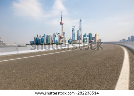 The fuzzy Asphalt road in front of the modern city Shanghai china - stock photo