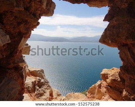 The gap of wonder. Beautiful view through a hole in the medieval walls of the mountaintop Palamidi Fortress in Nafplio, Greece Spring 2013