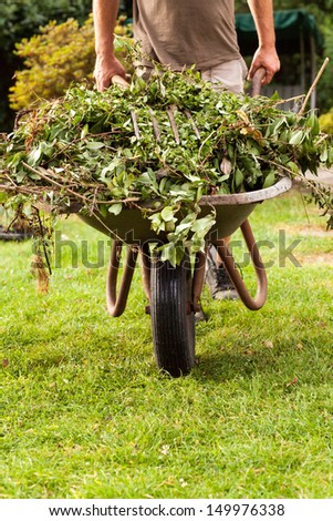 The gardener is banking the barrow over the grassland. - stock photo