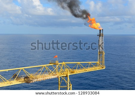 The gas flare is on the offshore oil rig platform. - stock photo