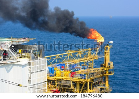 The gas flare is on the offshore oil rig platform - stock photo