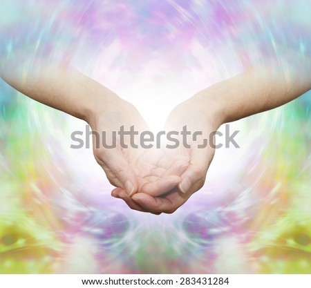 The Gentle Healer - Female with cupped hands emerging from a beautiful ethereal multicolored energy field background  - stock photo