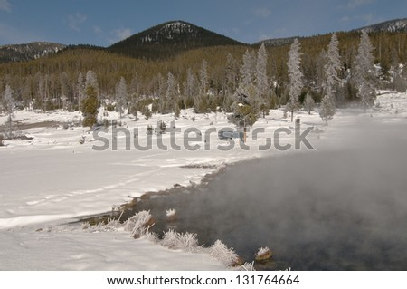 The geyser basin steams in the extreme cold in Yellowstone National Park - stock photo