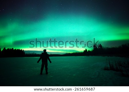 The ghostly colors of the aurora borealis captured above an unidentified person standing on a frozen lake in northern Canada