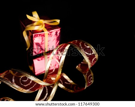 the gift in the red packaging ,delicate red ribbon on a black background with reflection - stock photo