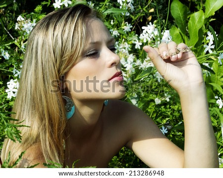 The girl among flowers with a thoughtful look. - stock photo
