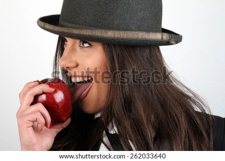 The girl and apple Beautiful young brunette with  a bowler hat on his head in a white shirt with a black tie in a black jacket holding red organic fresh apple and biting and licking provocative - stock photo