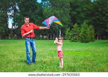 The girl and her father play with a kite. Dad devotes time to the child.