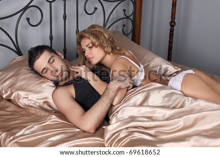The girl and the guy in a bed. The girl wants sexual relations, but the guy has fallen asleep