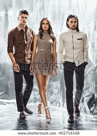 The girl and two young men on a silver background - stock photo