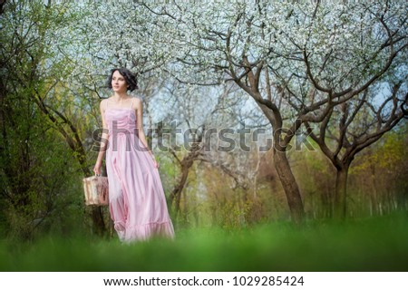 the girl as in a fairy tale runs through the flowering garden in the spring among the trees. He holds a chimodan in his hand and wears a long pink dress, looks aside