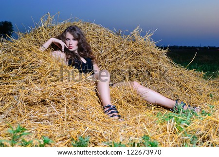 The girl at sunset on haystack - stock photo