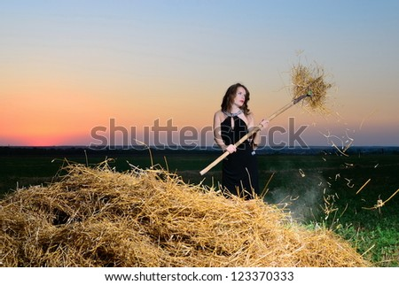 The girl at sunset with a pitchfork at a haystack