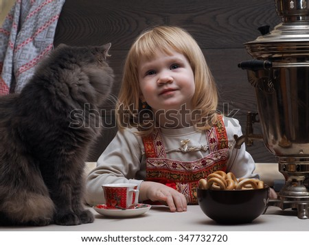 The girl at the samovar, in the countryside. On the table sits a cat. Bowl with bagels. A cup of tea. Samovar. Delicious tea. Girl dressed in sundress - Russian national clothes  - stock photo