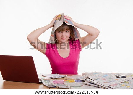 The girl at the table with a newspaper on his head - stock photo