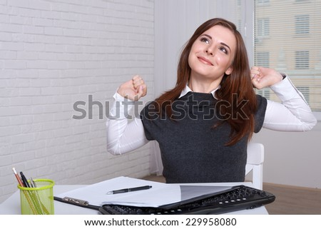 The girl at the workplace tired of work stretches - stock photo