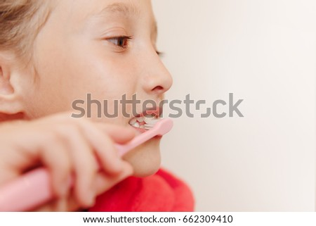 The girl brushes teeth in a bathroom