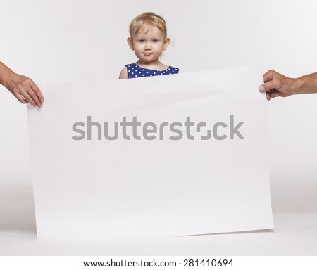 The girl child with a large poster on a white background - stock photo