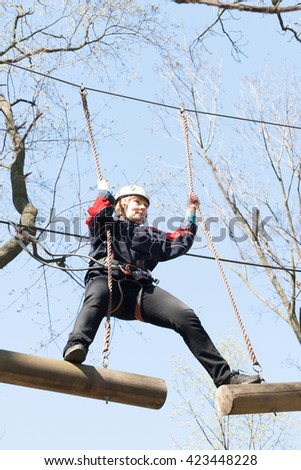 the girl climbs obstacles of rope park in clear summer day