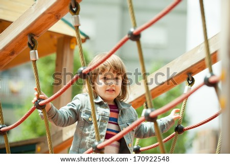 The girl climbs the ropes on the playground - stock photo