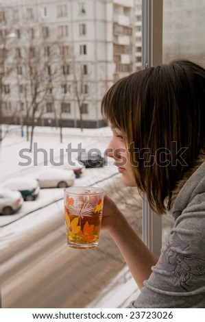 The girl costs on a balcony at an open window and drinks hot tea. Behind a window winter.